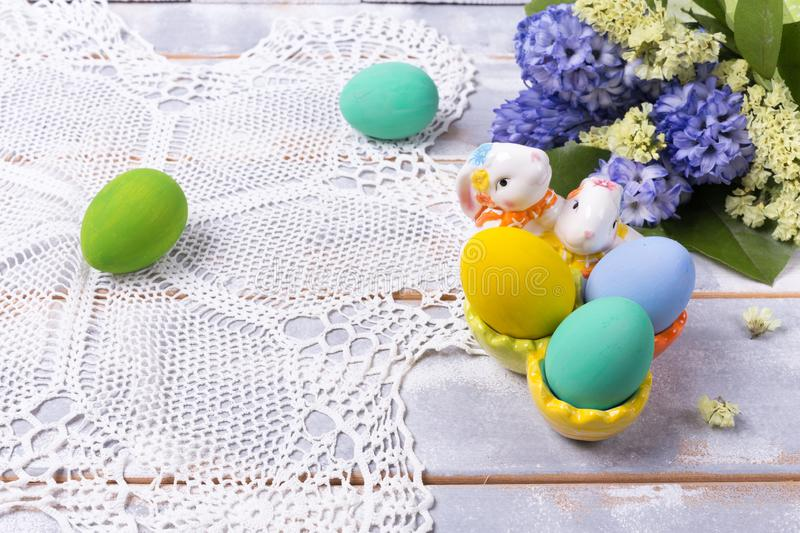 Colorful Easter eggs in a ceramic rabbit stand and a spring bouquet with lilac and yellow flowers on a beautiful knitted napkin on royalty free stock images