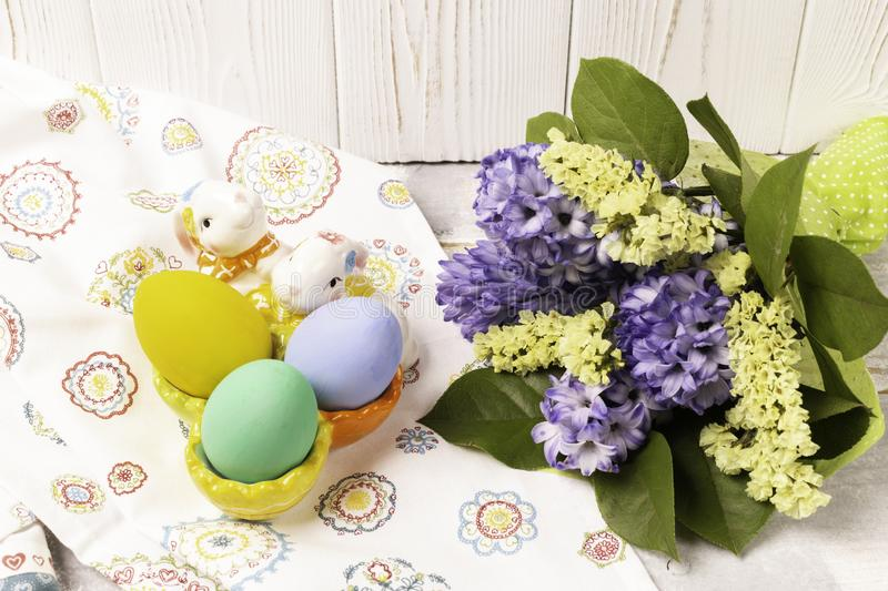 Colorful Easter eggs in a ceramic rabbit stand and a spring bouquet with purple hawths and yellow flowers on a white royalty free stock photo
