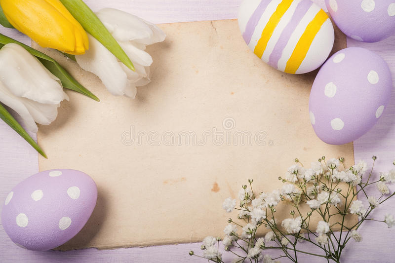 Colorful Easter eggs and flowers on old sheet of paper royalty free stock photos
