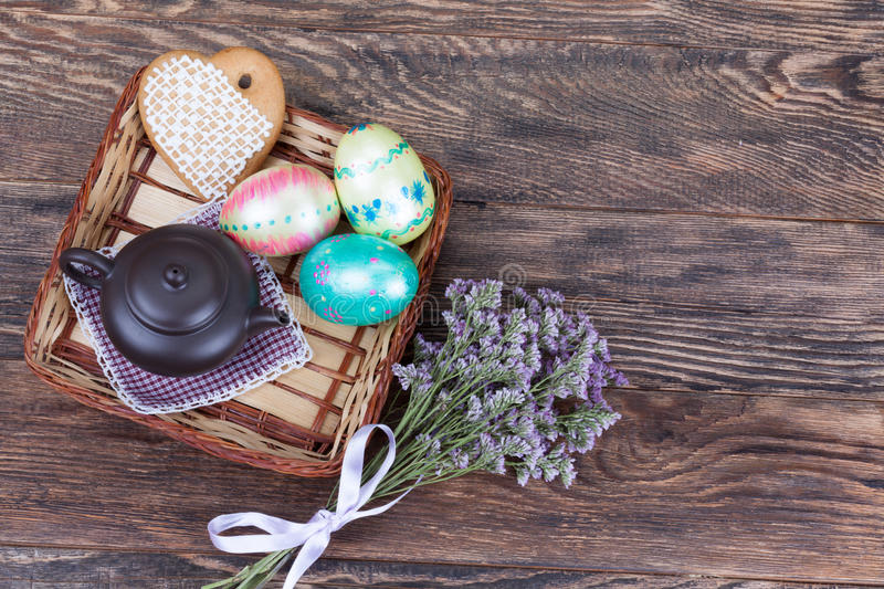 Colorful Easter Eggs with flowers and tea pot on wood stock photo