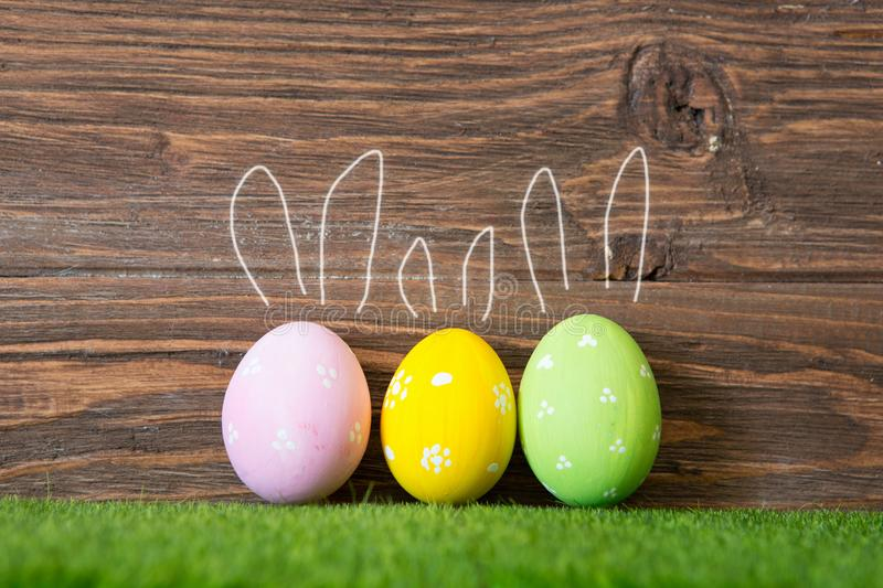 Colorful Easter eggs on grass with painted rabbit ears on wooden background royalty free stock photo