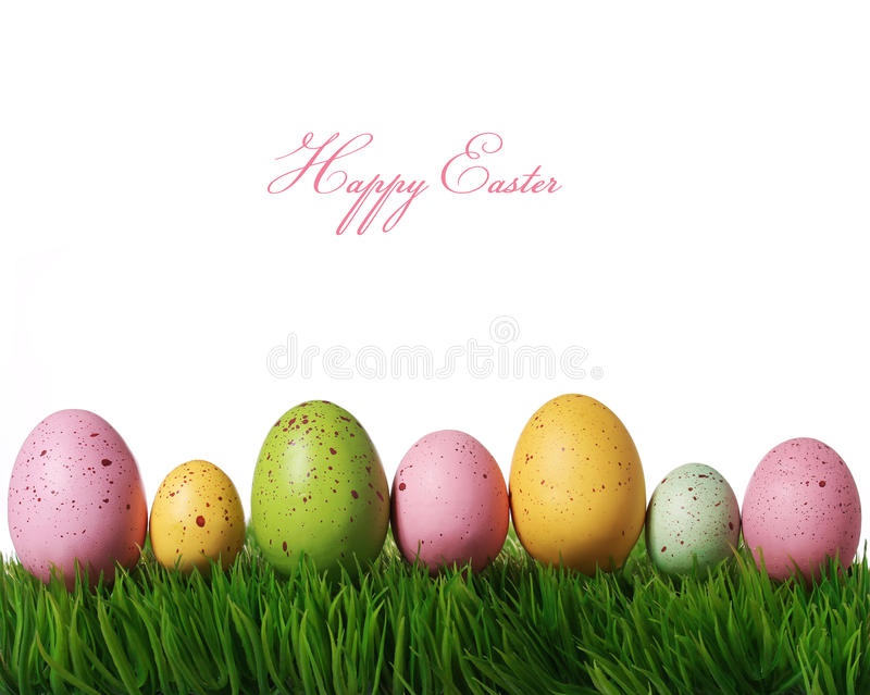 Colorful easter eggs on green grass isolated on white royalty free stock photography
