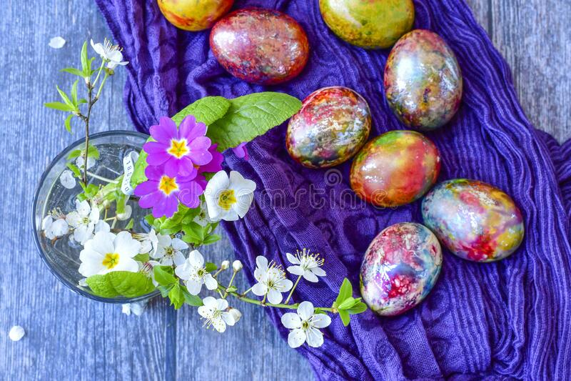 Colorful Easter eggs. Colorful easter hand painted eggs and spring blossom on wooden background stock image