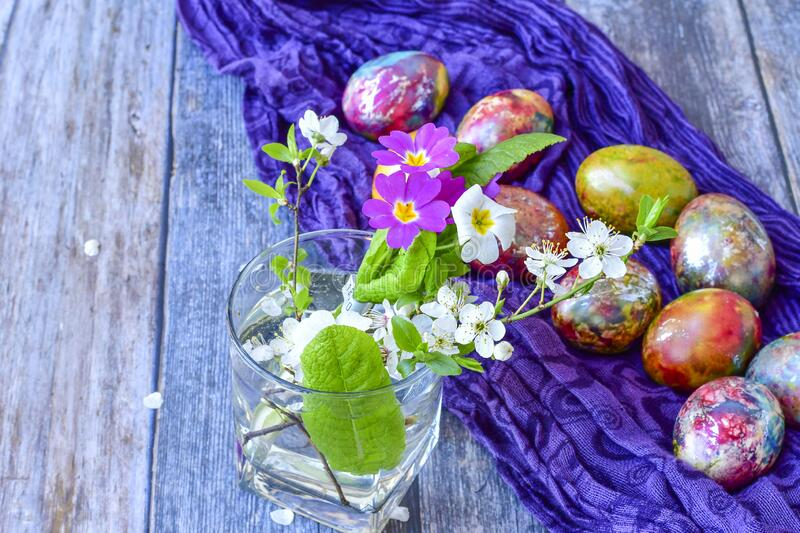 Colorful Easter eggs. Colorful easter hand painted eggs and spring blossom on wooden background royalty free stock image