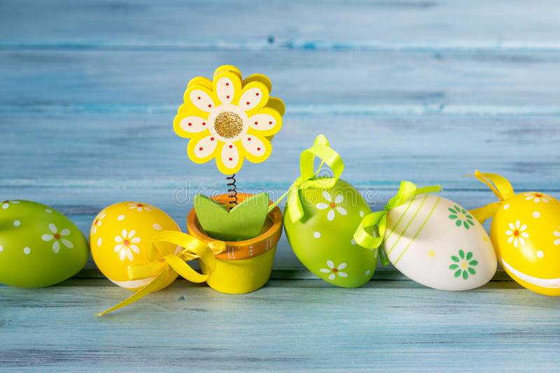 Colorful easter eggs in a line and flower note holder on blue wooden background stock photography