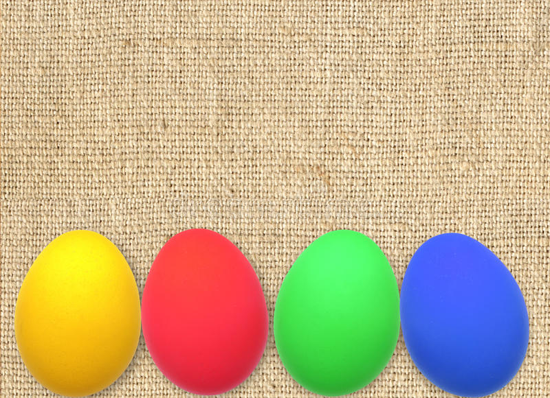Colorful Easter Eggs on linen burlap canvas texture stock photos