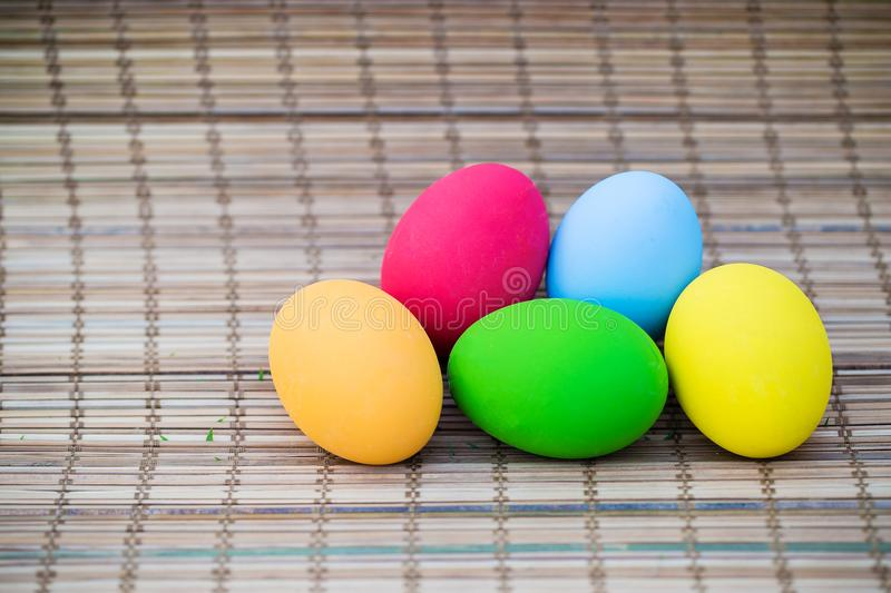Colorful easter eggs on nature bamboo mat background. symbol of easter`s day festival. vivid color natural background. festive wal. Lpaper. image for background royalty free stock images