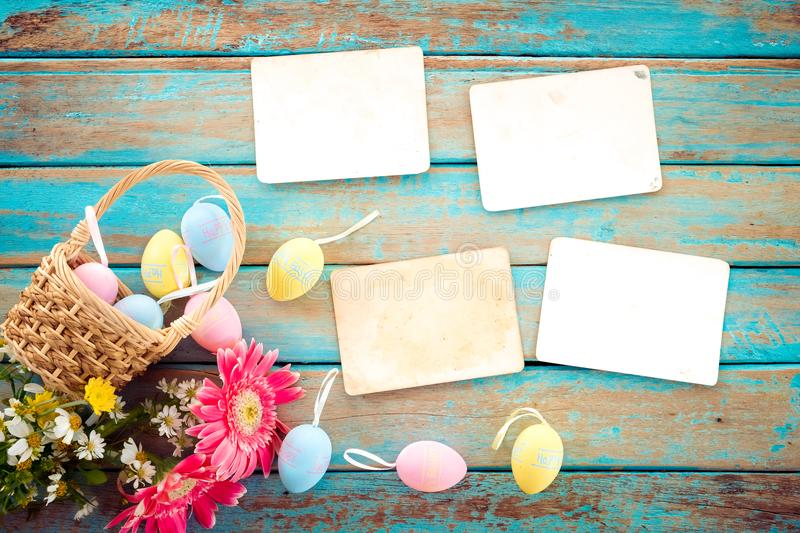 Colorful Easter eggs in nest with flower and empty old paper photo album on wood table royalty free stock images
