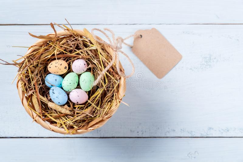Colorful Easter Eggs in nest of straw with tag on blue wooden background royalty free stock photo