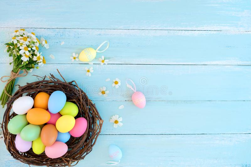 Colorful Easter eggs in nest with wildflowers on on rustic wooden planks background in blue paint. stock photography
