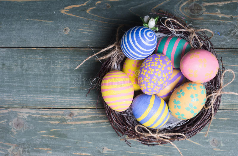 Colorful easter eggs. In nest on wooden background stock photography