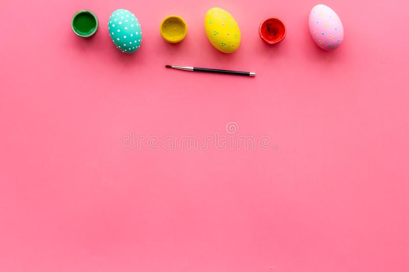 Colorful Easter eggs and paint for celebration on pink background top view mock up royalty free stock image