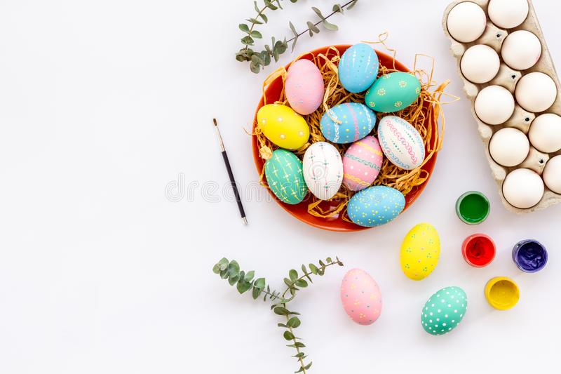 Colorful Easter eggs and paint for celebration on white background top view mock up royalty free stock photos