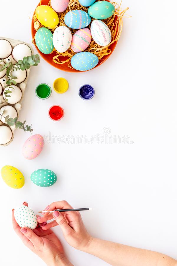 Colorful Easter eggs and paint for celebration on white background top view mock up stock images