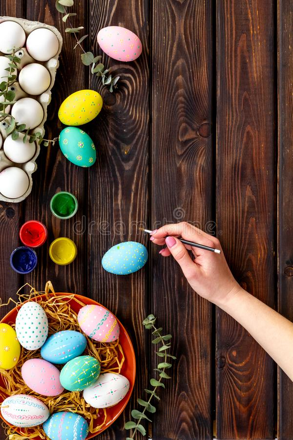 Colorful Easter eggs and paint for celebration on wooden background top view mock up stock image