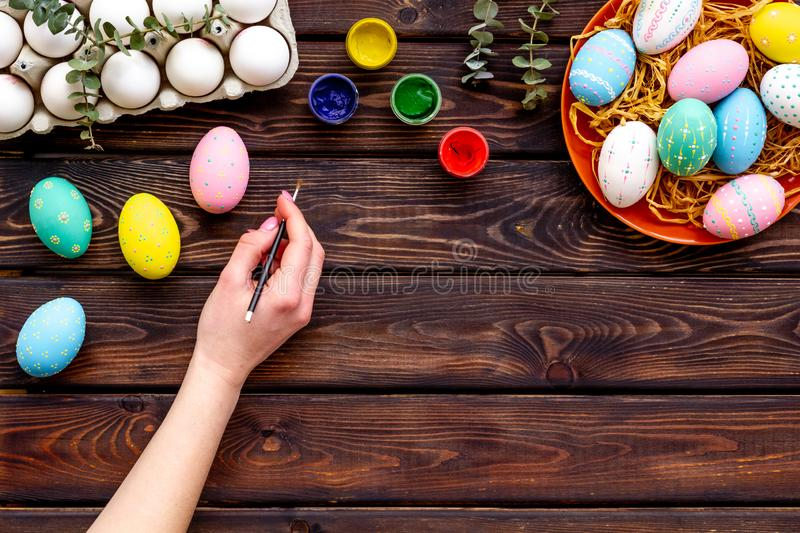 Colorful Easter eggs and paint for celebration on wooden background top view mock up royalty free stock photography