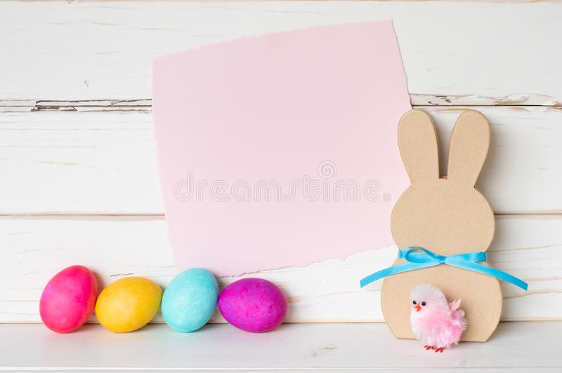 Colorful Easter Eggs with Pink Paper Invite Card and a Simple Bunny and Chick against White Shiplap Board Background wall. With room or space for copy, text or royalty free stock photo
