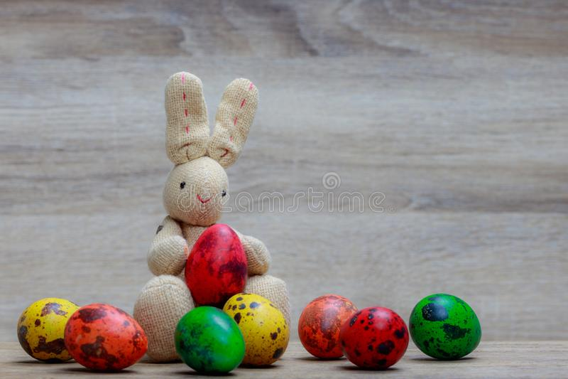 Colorful easter eggs and rabbit doll on wooden background. stock photos
