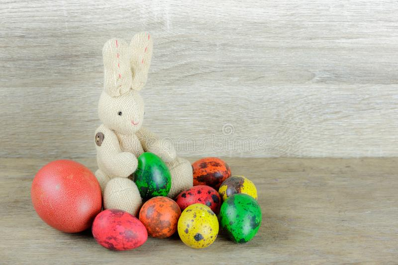 Colorful easter eggs and rabbit doll on wooden background. royalty free stock photos