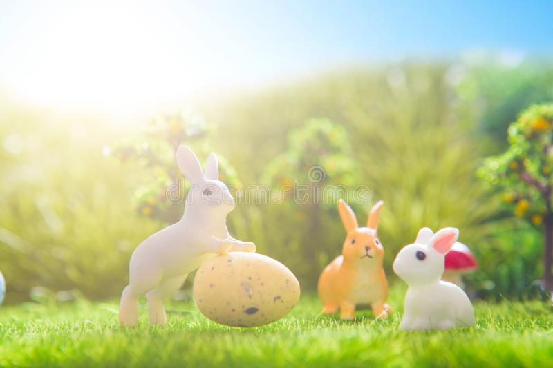 Colorful Easter eggs and rabbits toys on green grass. Fairy tale.  stock photography