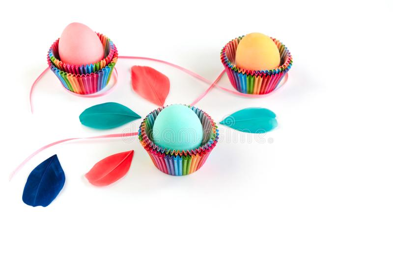 Colorful Easter eggs in raibow colored paper forms for cupcakes on white background. stock photography