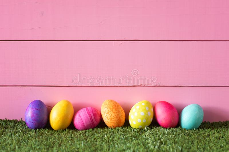Colorful Easter Eggs in Row on Bottom of Pink Wood Boards Wall Background and Laying in Green Grass with room or space for copy royalty free stock photography