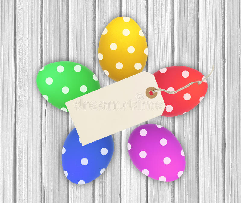Colorful Easter Eggs with tag card over wooden background royalty free stock photos