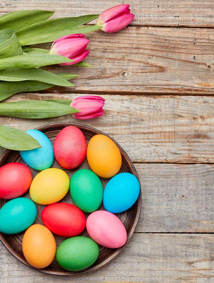 Colorful easter eggs and tulips on wooden background royalty free stock image