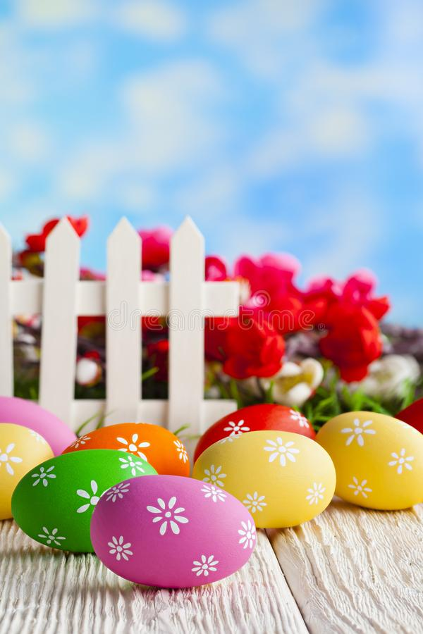 Colorful Easter eggs and white fence on nature background stock photography