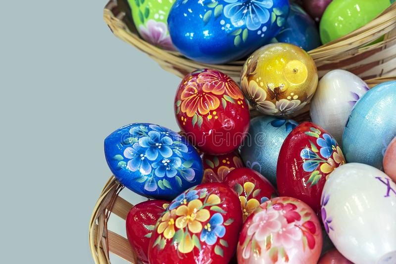 Colorful Easter eggs in a wicker basket on a gray background royalty free stock images