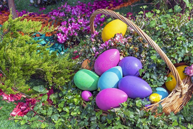 Colorful Easter eggs in a wicker basket on a natural background royalty free stock image
