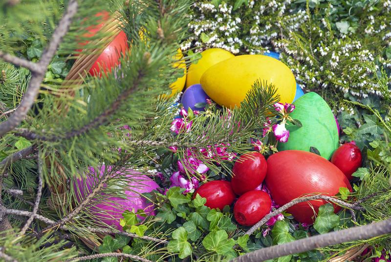 Colorful Easter eggs in a wicker basket on a natural background royalty free stock photos