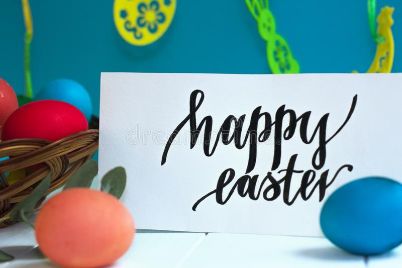 Colorful Easter eggs in a wicker basket and on a white background, text Happy Easter stock photography