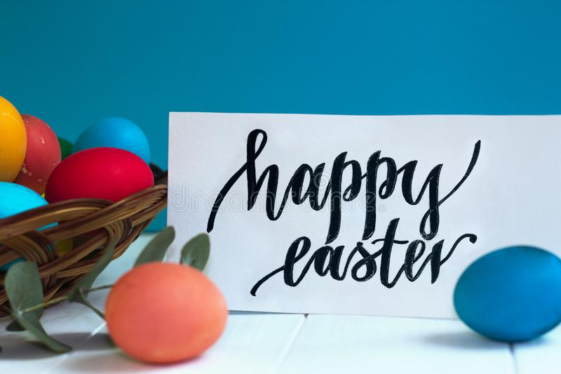 colorful Easter eggs in a wicker basket and on a white background, text Happy Easter stock image