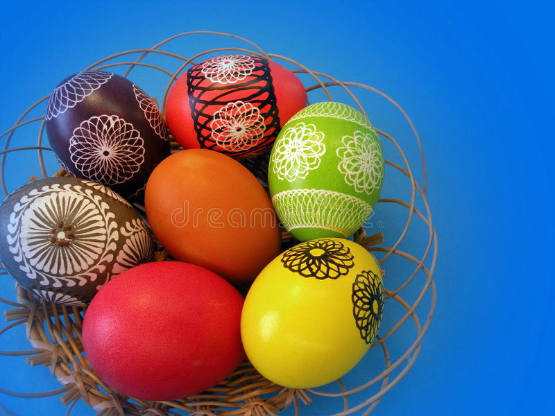 Colorful Easter eggs. In wicker on blue background stock photography