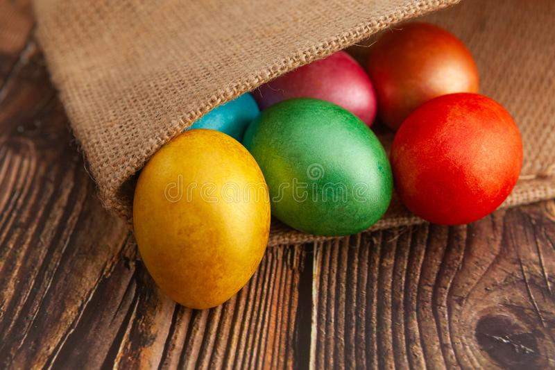 Colorful Easter eggs on a wooden background in burlap, close-up royalty free stock photos
