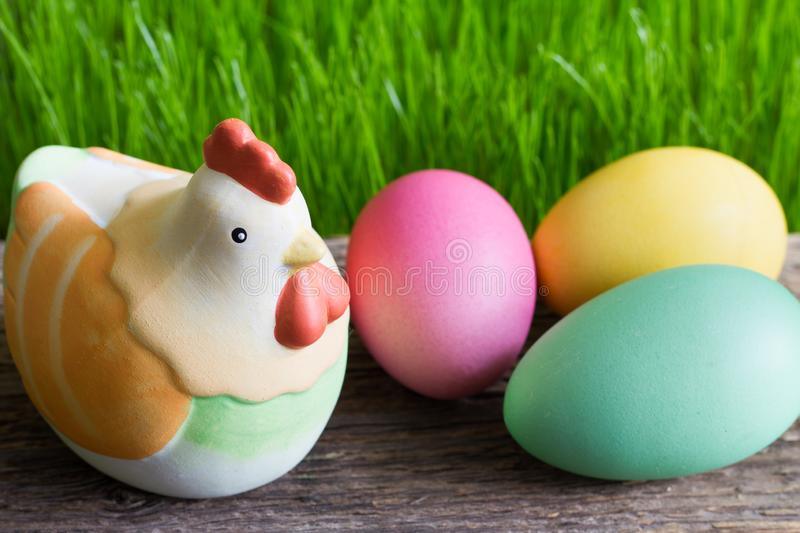 Colorful easter eggs on wooden plank and green grass. Closeup stock images