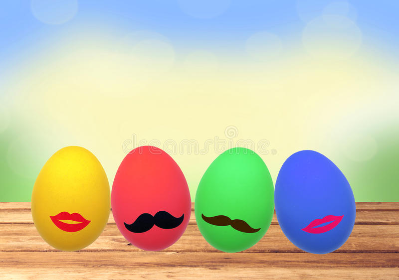 Colorful Easter eggs on wooden table over nature stock photography