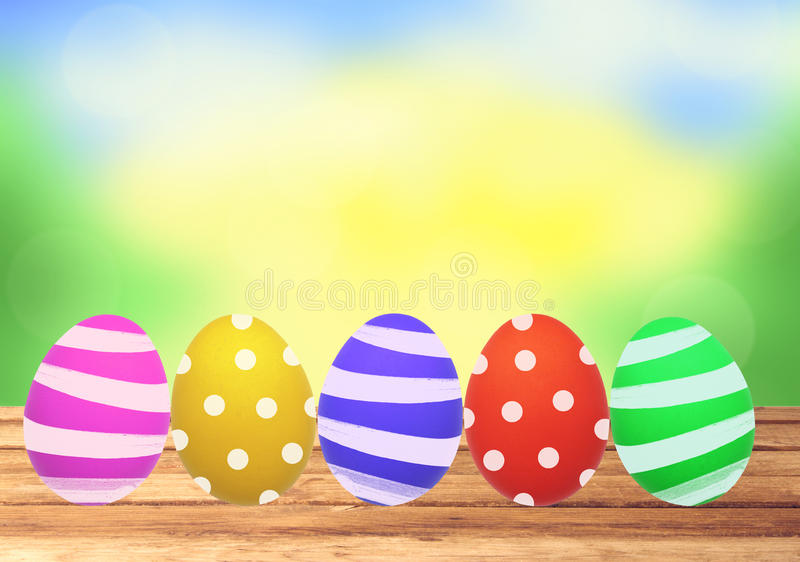 Colorful Easter eggs on wooden table over nature stock photos