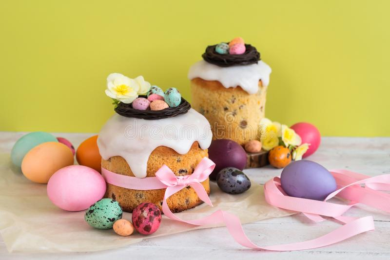 Colorful Easter spring stillife in soft light and trendy pastel colors. Traditional cake with chocolate nest, candy and qail eggs. Decoration blossom flowers on stock photography