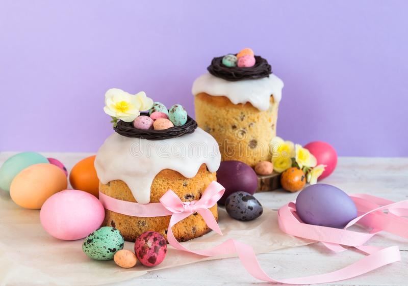 Colorful Easter spring stillife in soft light and trendy pastel colors. Traditional cake with chocolate nest, candy and qail eggs. Decoration blossom flowers on royalty free stock image