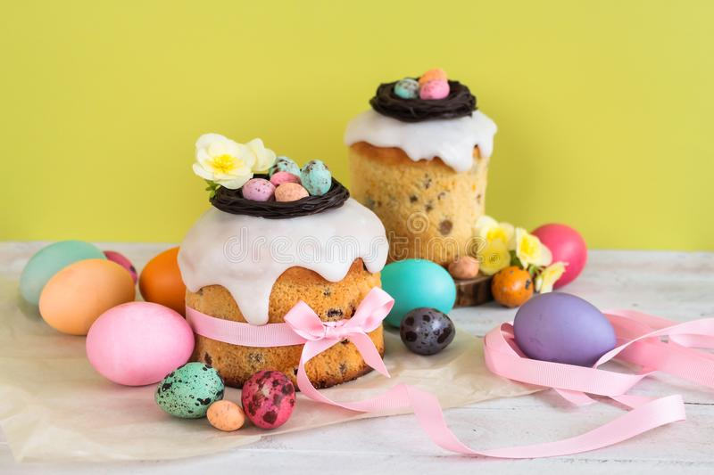 Colorful Easter spring stillife in soft light and trendy pastel colors. Traditional cake with chocolate nest, candy and qail eggs. Decoration blossom flowers on stock photos