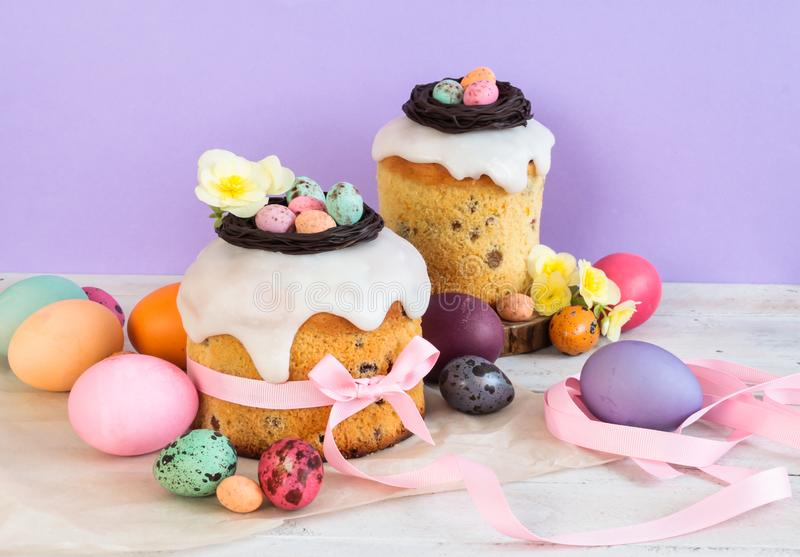 Colorful Easter spring stillife in soft light and trendy pastel colors. Traditional cake with chocolate nest, candy and qail eggs. Decoration blossom flowers on stock images