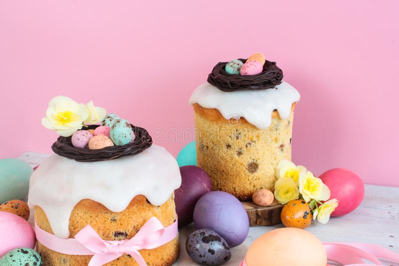 Colorful Easter spring stillife in soft light and trendy pastel colors. Traditional cake with chocolate nest, candy and qail eggs. Decoration blossom flowers on royalty free stock photo