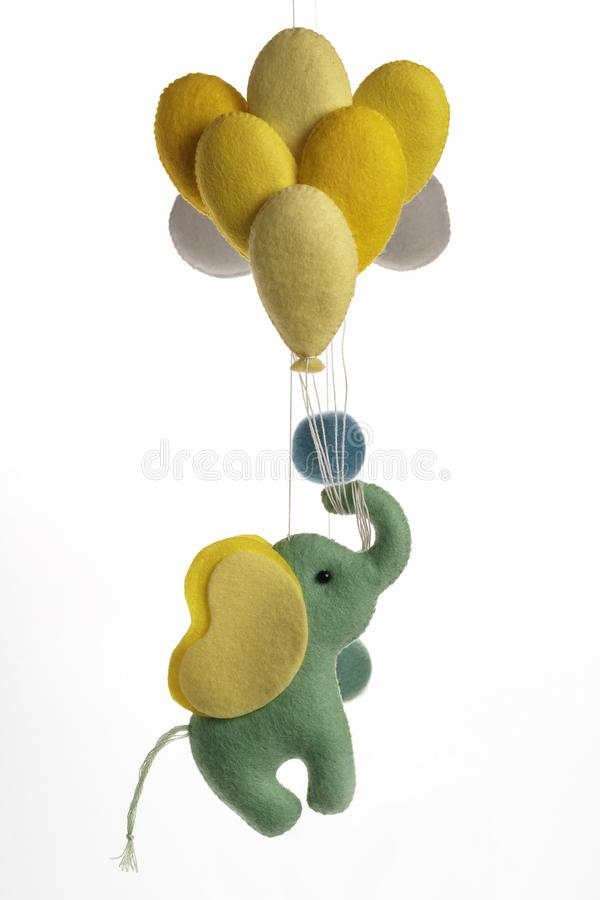 Colorful and eco-friendly children`s mobile from felt. A felt toy in the form of a lovely elephant with baloons, part of a royalty free stock photography