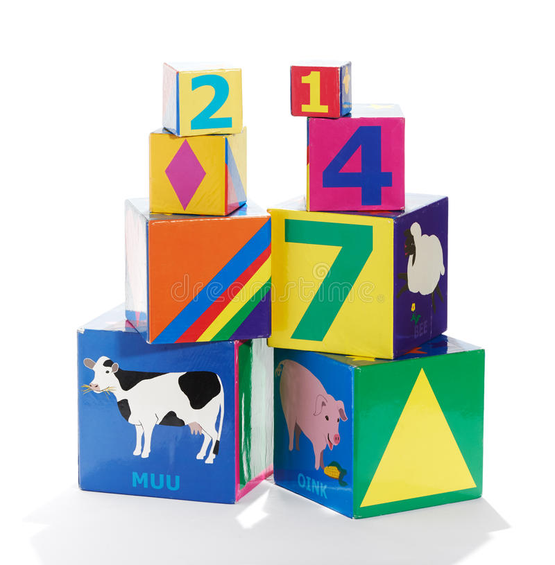 Colorful educational childrens building blocks. Colorful educational wooden childrens building blocks in different sizes with animals, patterns and numbers royalty free stock photos