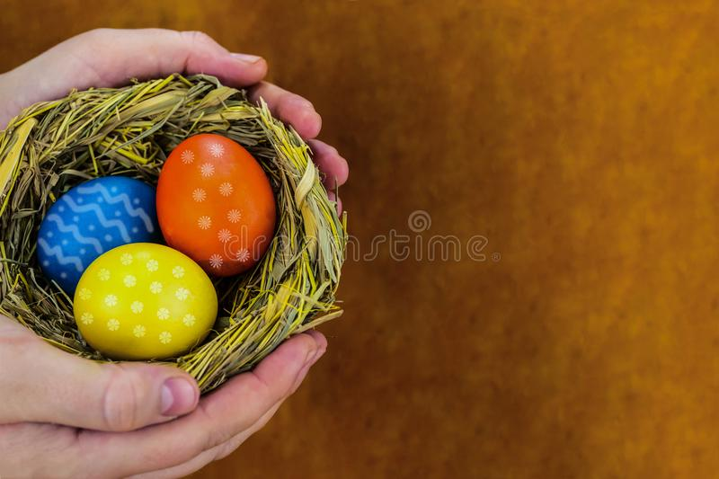 Colorful eggs blue yellow decorated ornament in a woven straw nest present in hands with copy space stock photos