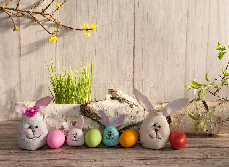 Colorful eggs, funny handmade Easter bunnies, grass and branches with leaves and flowers on a light wooden background. Easter composition. Colorful eggs, funny royalty free stock photos