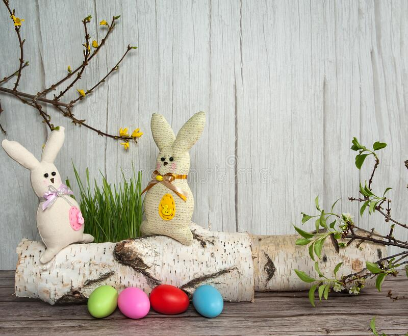 Colorful eggs, funny handmade textile Easter bunnies and spring branches with leaves and flowers on a light wooden background. Easter composition. Colorful eggs stock photo
