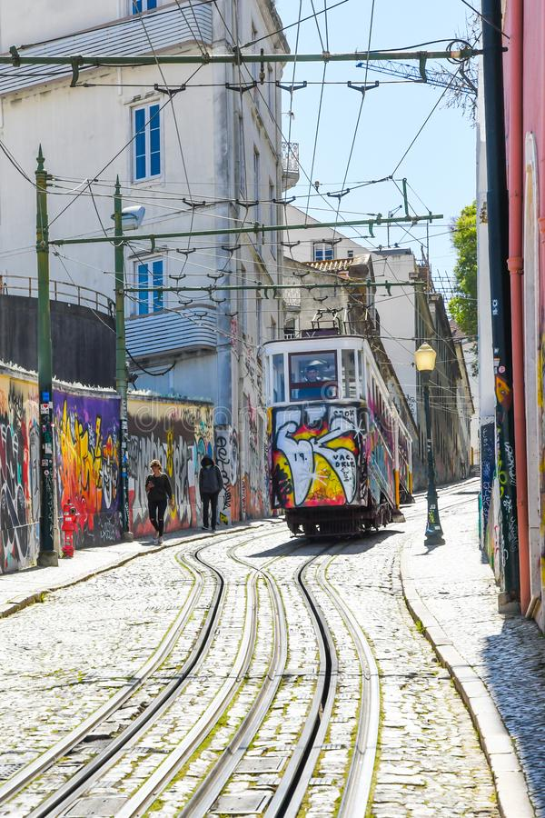 Colorful Elevador da Gloria going through narrow streets in Lisbon. Europe. Elevador da Gloria is a very old public transport vehicle similar to tram in Lisbon stock images